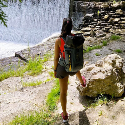 Woman wearing waterproof backpack at waterfall
