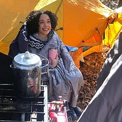 Woman keeping warm with blanket in front of tent.